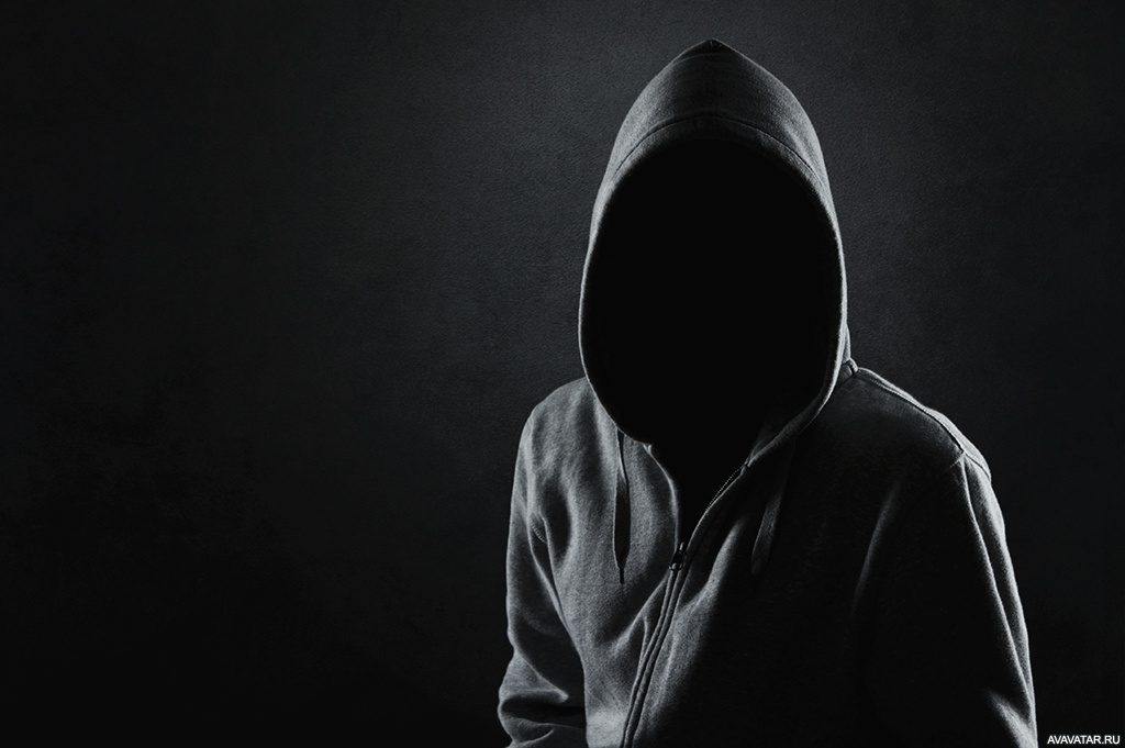 Человек в серой одежде с полностью скрытым под капюшоном ...